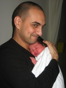 Only a few hours old, in her daddy's arms: Daddy went home for a quick nap that Thursday, and rushed back later that morning to hold her while I showered.