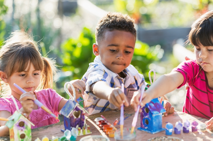 Multi-ethnic children (5 years) painting bird houses.