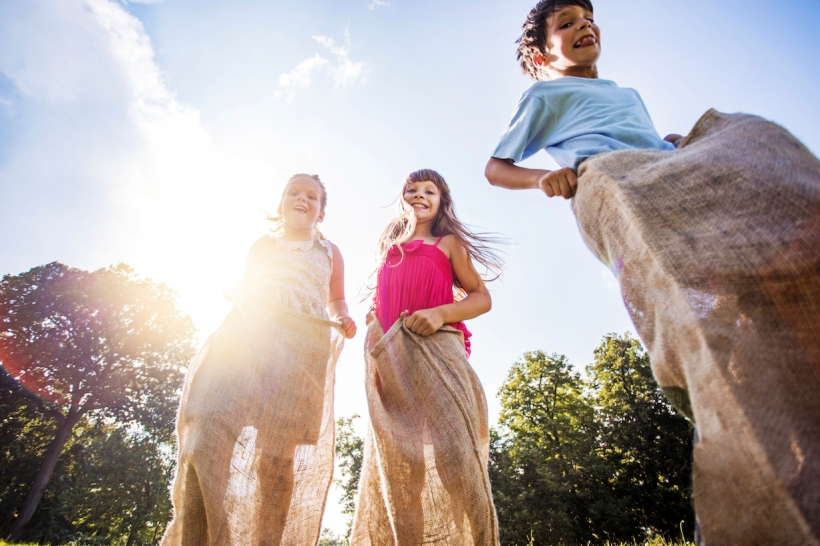 Low angle view of three happy children having fun in a sack race outdoors.
